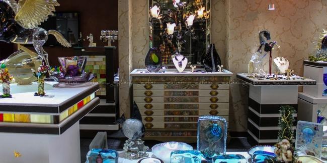 С 2009г. по сегодняшний день мы тесно сотрудничаем с фирмой ' DI MURANO', занимающейся поставкой и реализацией в Москве эксклюзивных изделий из стекла от ведущих мастеров с острова Мурано ( Италия). За прошедший период мы оформили для 'DI MURANO' несколько магазинов в Крокус Сити, в Смоленском Пассаже, Галереях Времена Года, DREAM HOUSE и Модном сезане. Для этого проекта мы не только разработали, изготовили и продолжаем совершенствовать торговое оборудование, но и всерьез озаботились решением сложной задачи максимально выигрышной подсветки стекла, что повлекло за собой рождение нескольких моделей светильников, которые мы изготовили и уже используем в освещении этих магазинов. Материалы, использованные при производстве оборудования: фанера, дуб, витражи, декоративные фактурные краски, ткани.